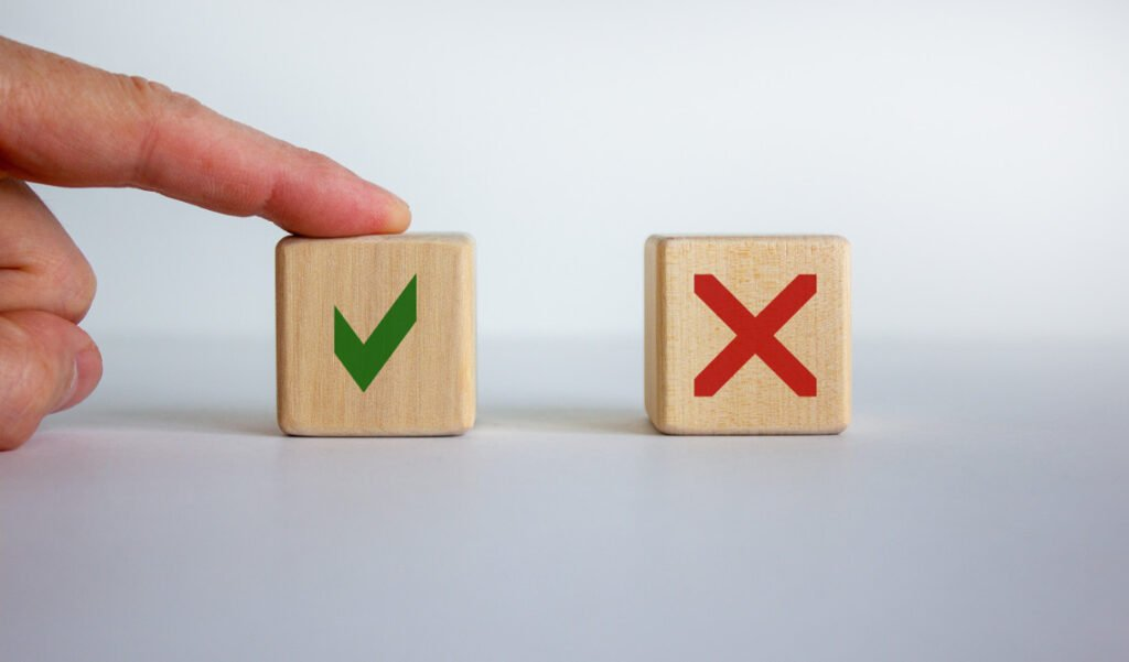 """Hand pointing to a wooden block with a green checkmark instead of the block with a red """"X"""".Making Right Choice about foundation repair."""