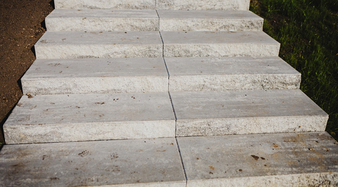 Gray concrete stairs sinking into ground